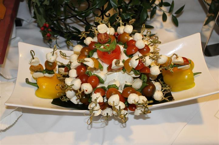 Cheese balls with cherry tomatoes on skewers on bed of peppers