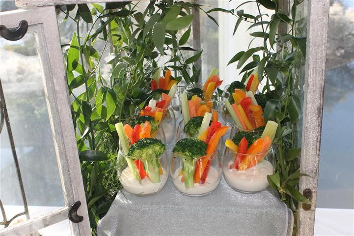 Celery, carrots, peppers, broccoli in ranch dressing glass.