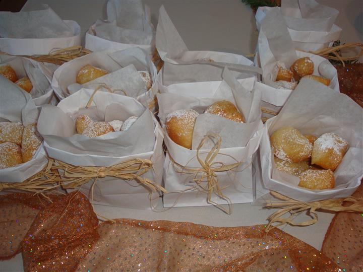 Fried dough with powdered sugar in tied paper baggies.