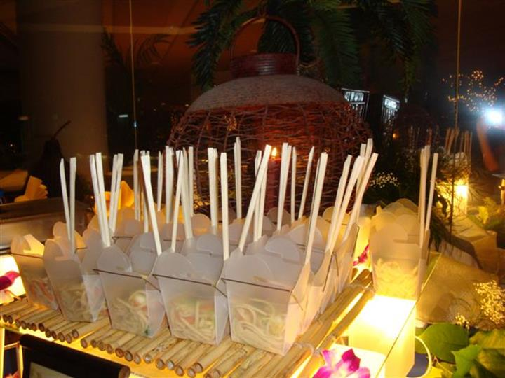 noodles in containers with chop sticks on illuminated light box