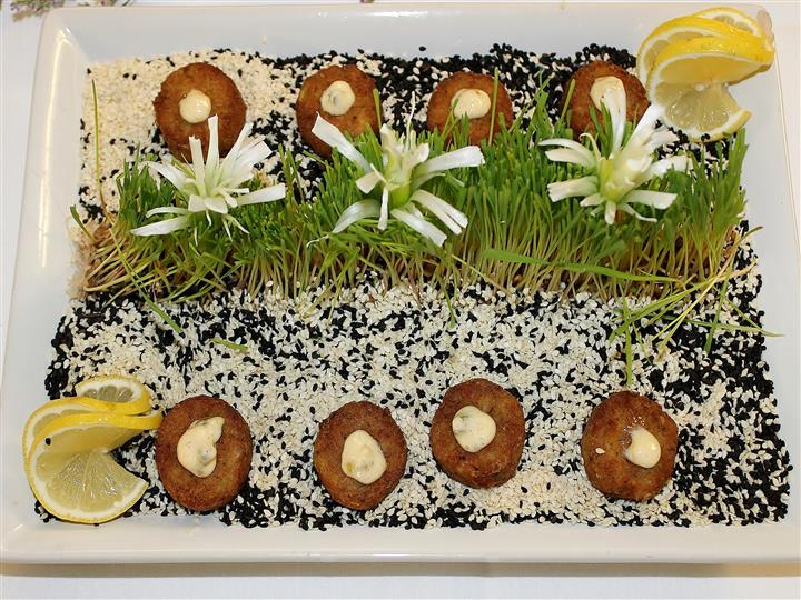 Miniature potato pancake with creme fraiche over bed of sesame seeds