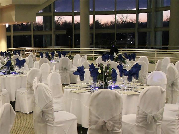 Reception hall with white clothed tables and chairs