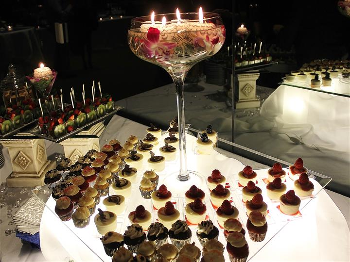 Assorted desserts and fruit cups around tall stemmed glass with candles