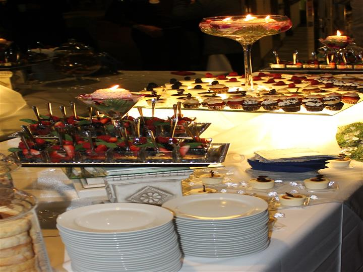 Assorted desserts and fruit cups around tall stemmed glass with candles next to stack of dishes
