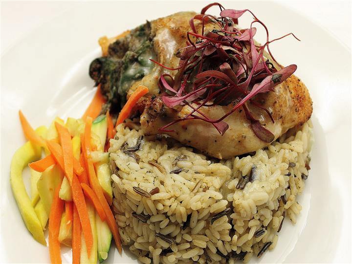Chicken over cooked rice and vegetables