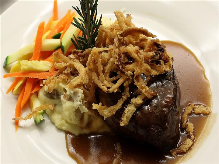 Meat with gravy, mashed potatoes, onion straws, side of vegetables