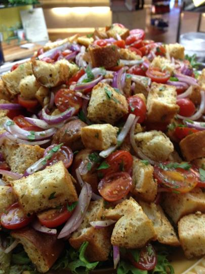 large salad topped with croutons, onions, tomatoes, and herbs