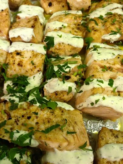 tray of baked fish fillets with sauce and herbs