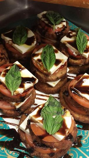fried eggplant stacked together with tomatoes, cheese, vinaigrette and basil leaves
