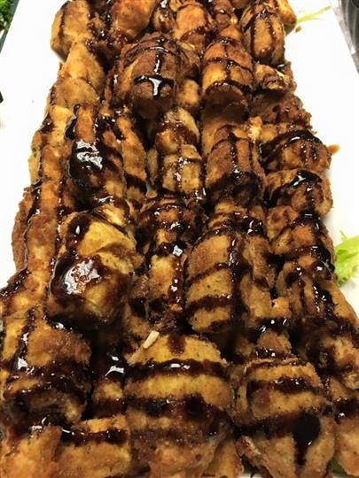 sheet tray of fried dessert topped with chocolate sryup