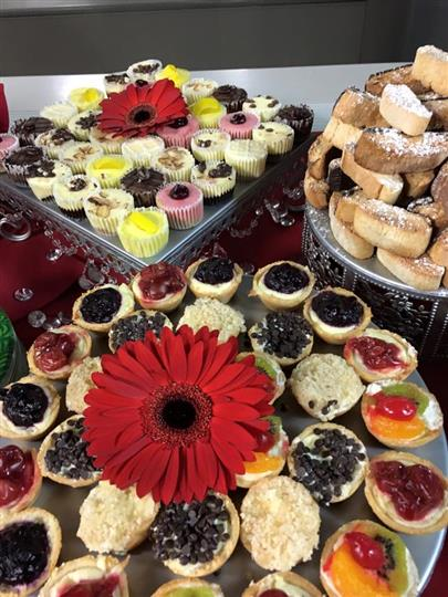various assortment of cupcakes, desserts all topped with powered sugar and decorated with flower pedals