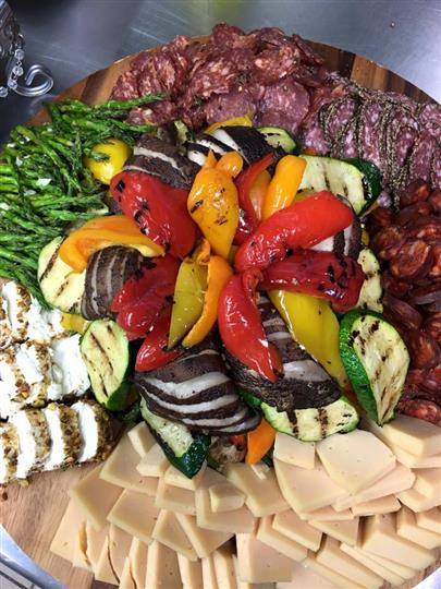 platter assortment of various cheeses, meats and grilled vegetables
