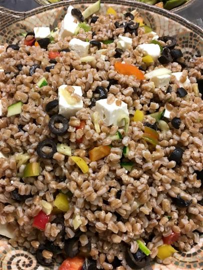 barley salad with feta cheese, olives, avacado and peppers