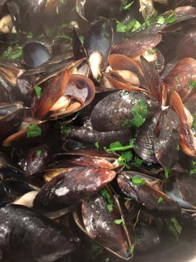 cooked mussels in a pot with herbs