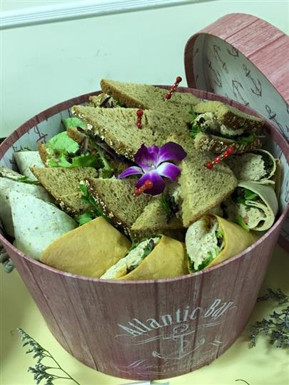 bucket filled with various subs and wraps with a decorative flower pedal