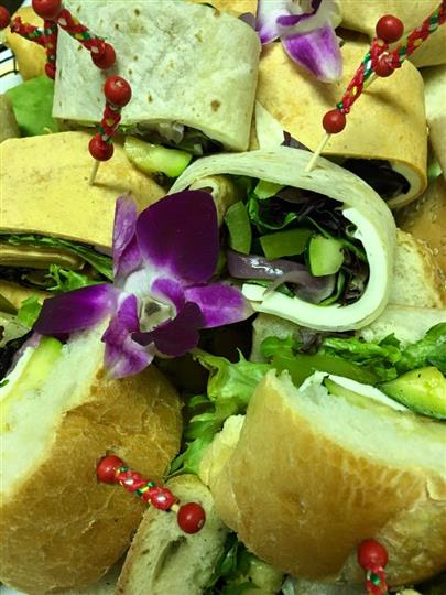catering tray of various subs and wraps with floral decorations