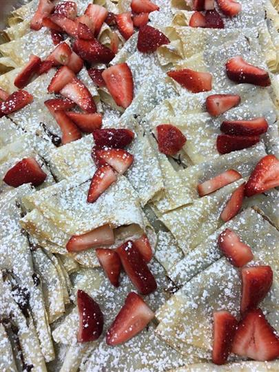 creepes topped with strawberries and powered sugar