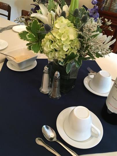 Table with flower centerpiece, placesettings and wine bottles