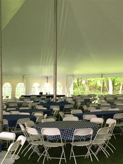 exterior setup under a tent with circular tables and chairs