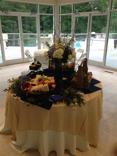 Display table with assorted meats and cheeses next to flower displays