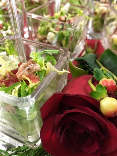 Baby green salads with crumbled cheese and walnuts on table next to roses