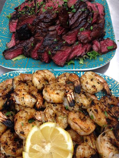 Cooked shrimp plate next to steak plate done medium rare