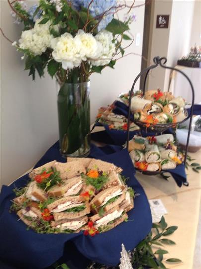 Assorted sandwiches and wraps in baskets next to vase of flowers