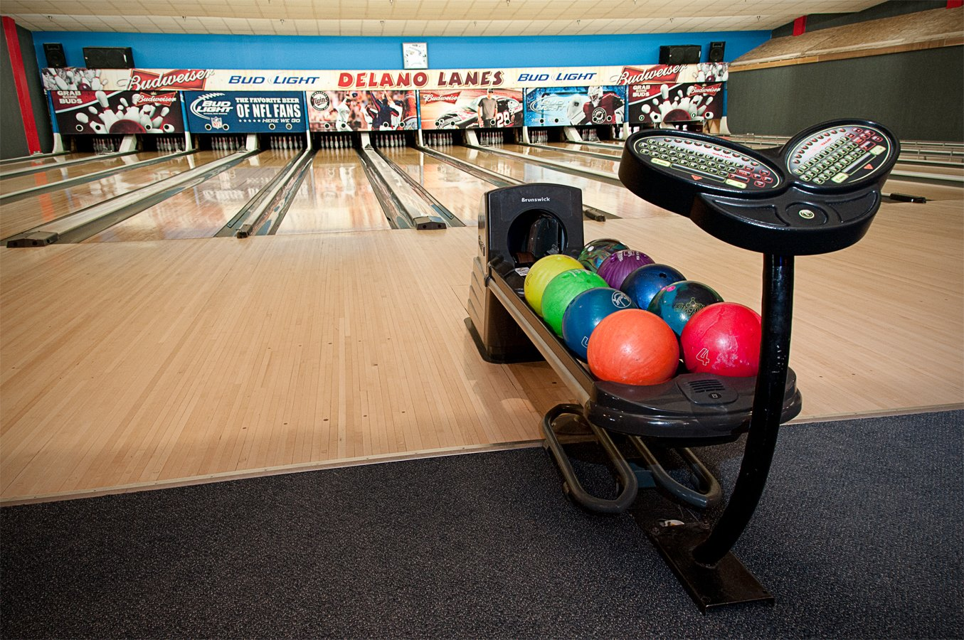 bowling balls on the rack and bowling alleys in the background