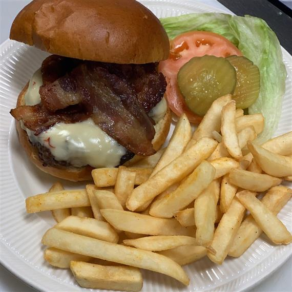 bacon cheeseburger with lettuce, tomato and pickles served with french fries