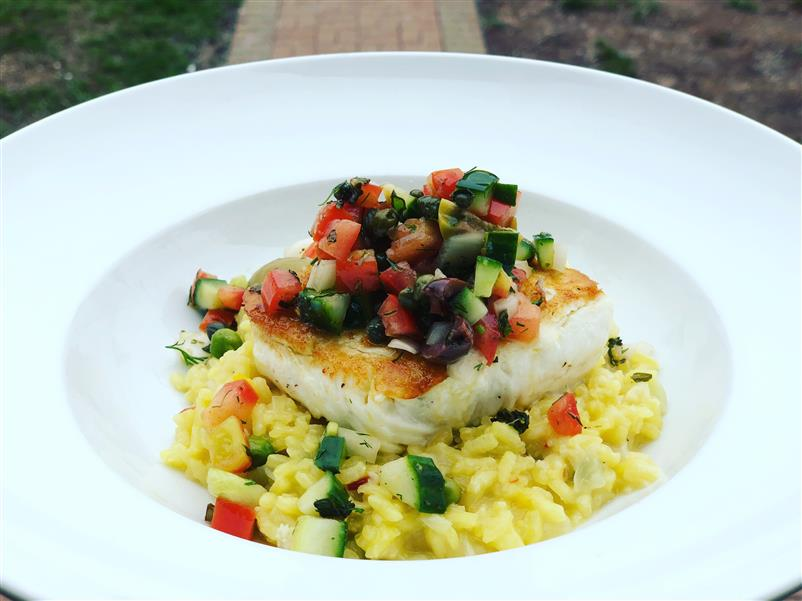 grilled fish on paella with chopped veggies on top