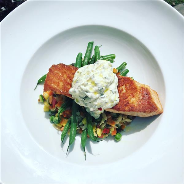 slice of grilled fish on a bed of string beans and mixed veggies