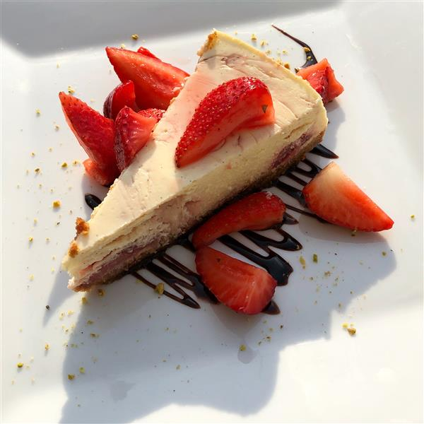 cheesecake on a plate with chocolate drizzle and sliced strawberries