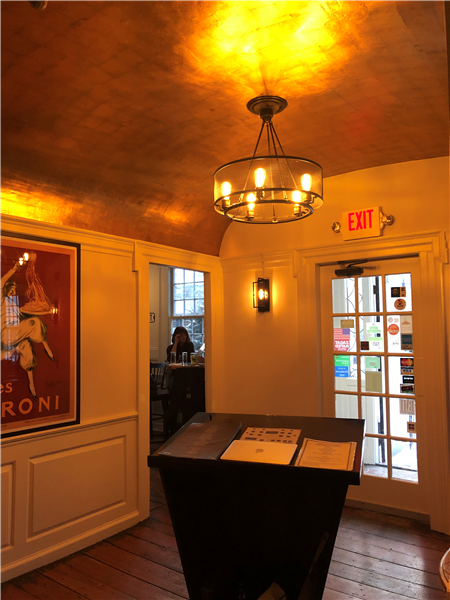 view of the host stand under a light fixture on the wall