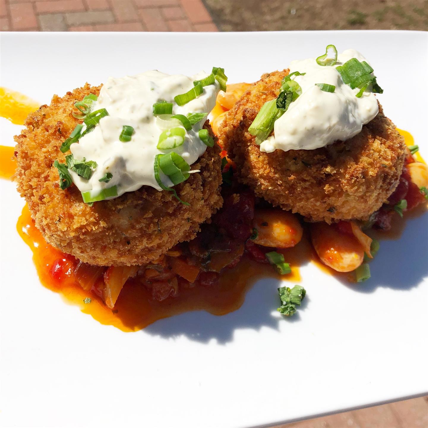 two crab cakes on a bed of veggies