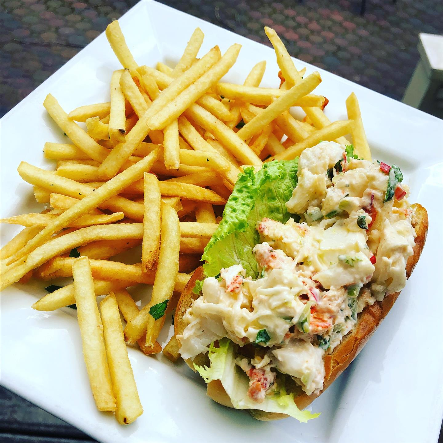 lobster roll on a toasted bun with a side of french fries