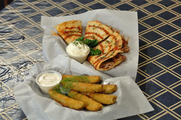 pulled pork quesadilla topped with sriracha with a side of sour cream and mozzarella sticks with a side of dipping sauce
