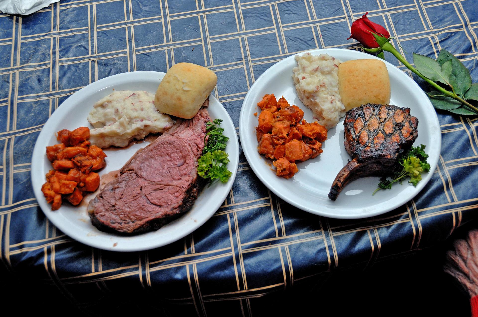 two dishes on a table with grilled meat with a side of mashed potatoes, biscuit and sweet potatoes
