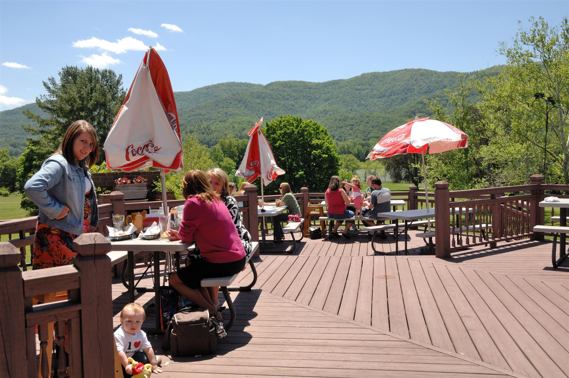 outside deck area with tables and umbrellas and a few people