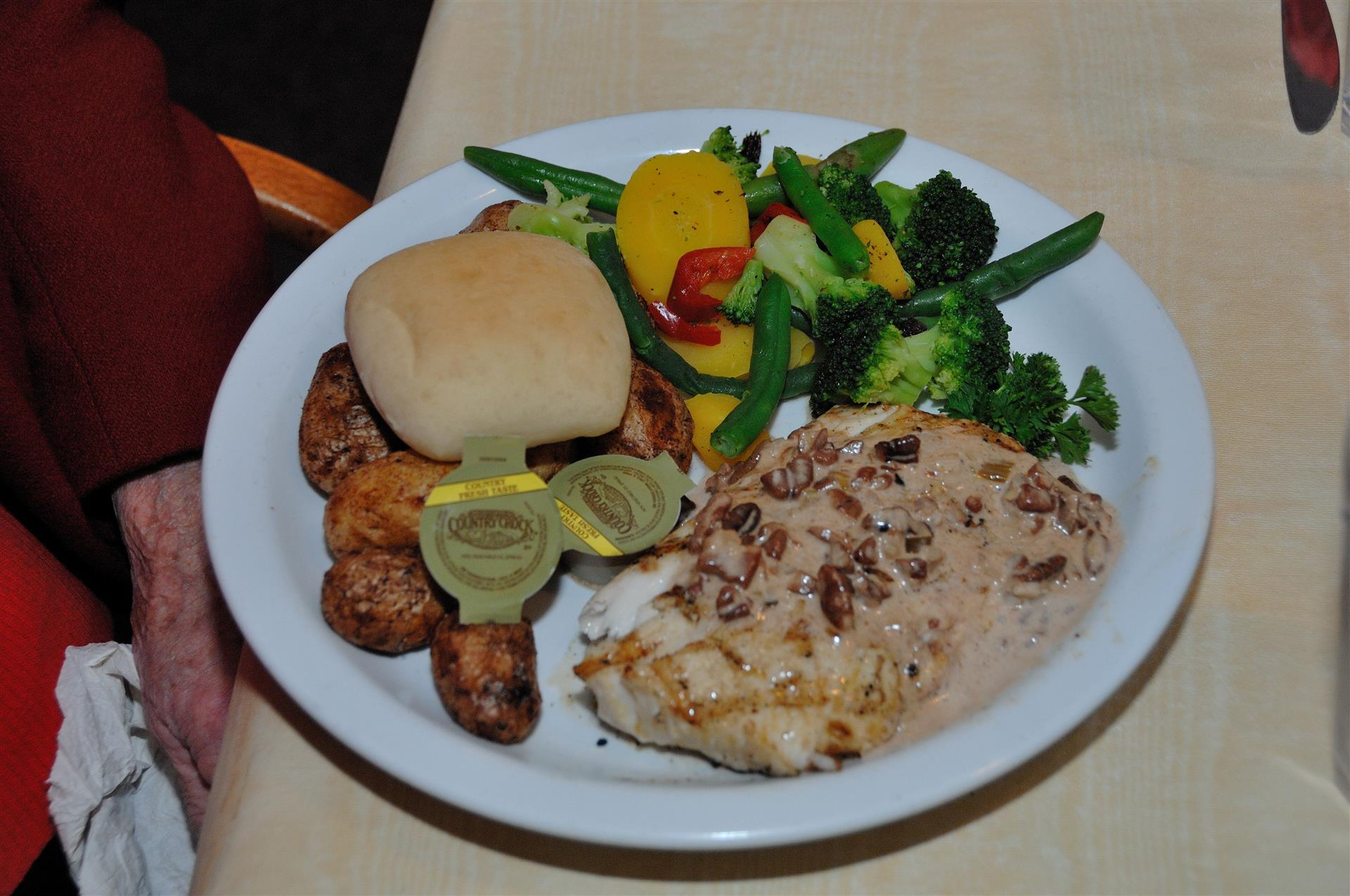 grilled salmon topped with sauce and nuts with a side of potatoes, veggies, and a biscuit with butter