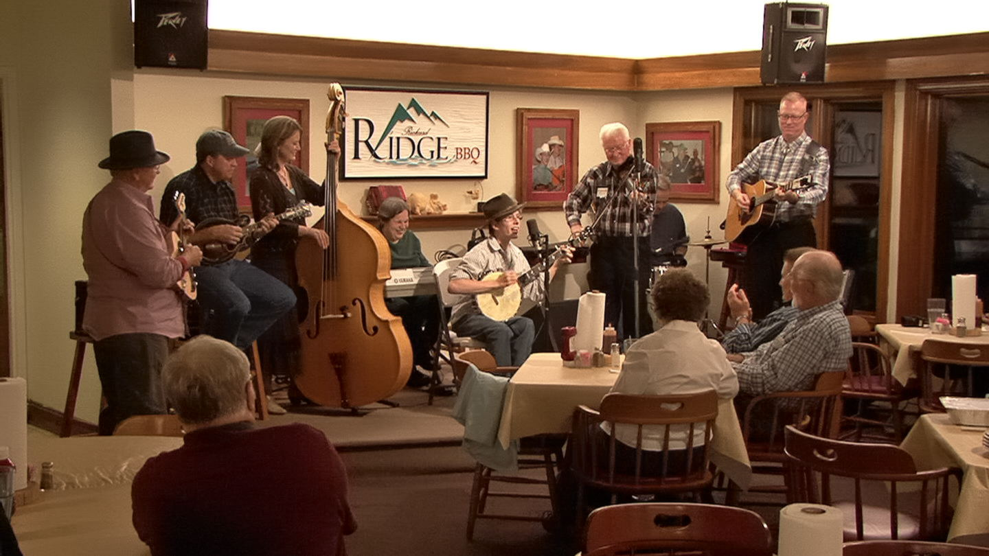people in dining room watching a band playing instruments on stage
