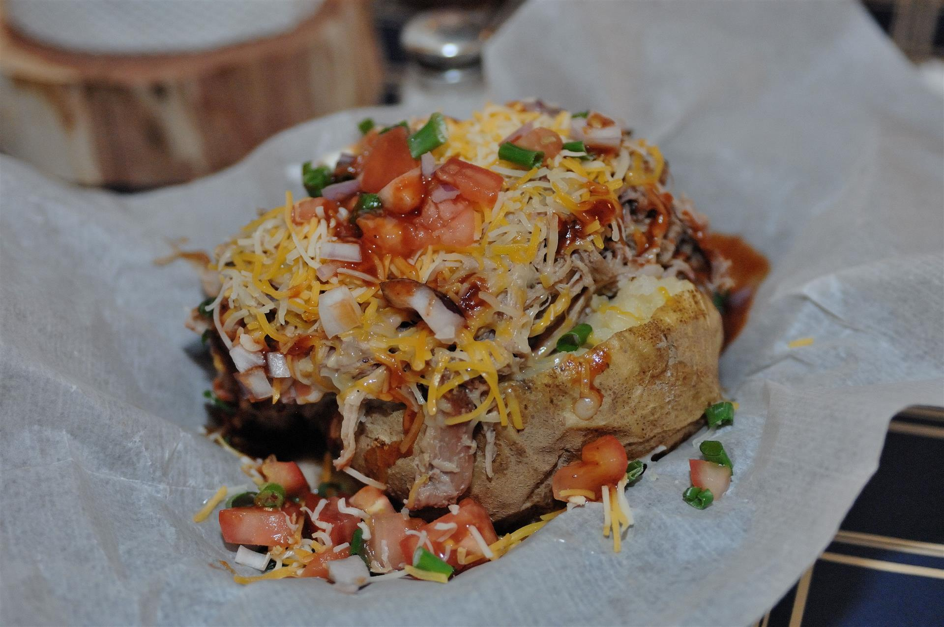 baked potato topped with pulled pork, tomatoes, shredded cheese, onions,  and chives