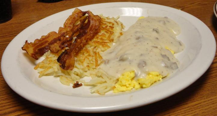 Hash browns served with bacon and scrambled eggs with gravy