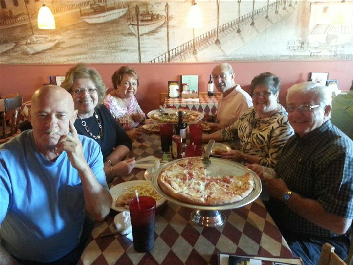 a group of happy customers smiling with their pizza pie