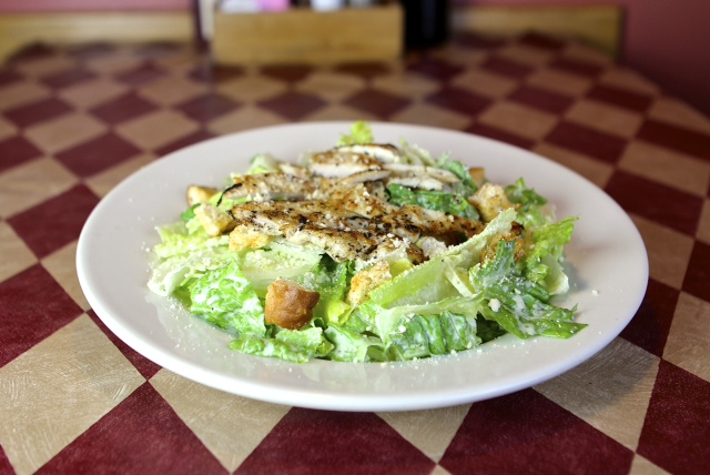 a caesar salad with grilled chicken