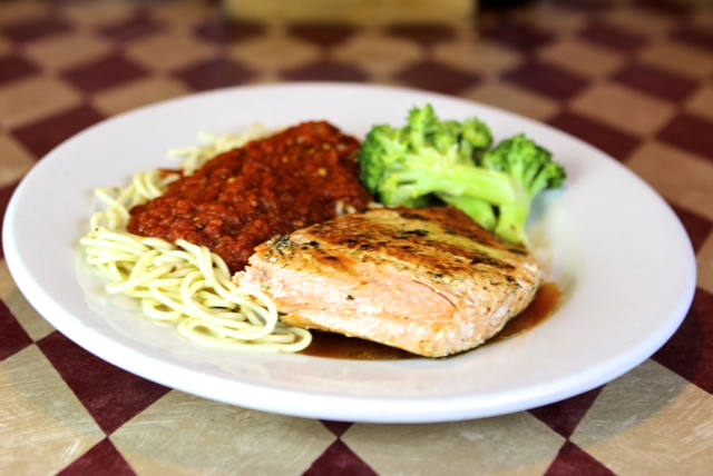 a spaghetti with marinara with salmon and a side of broccoli