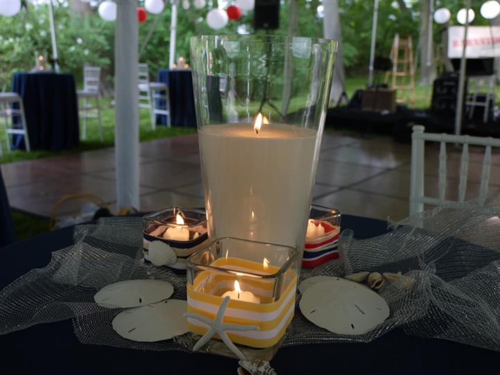several candles on a table with seashells