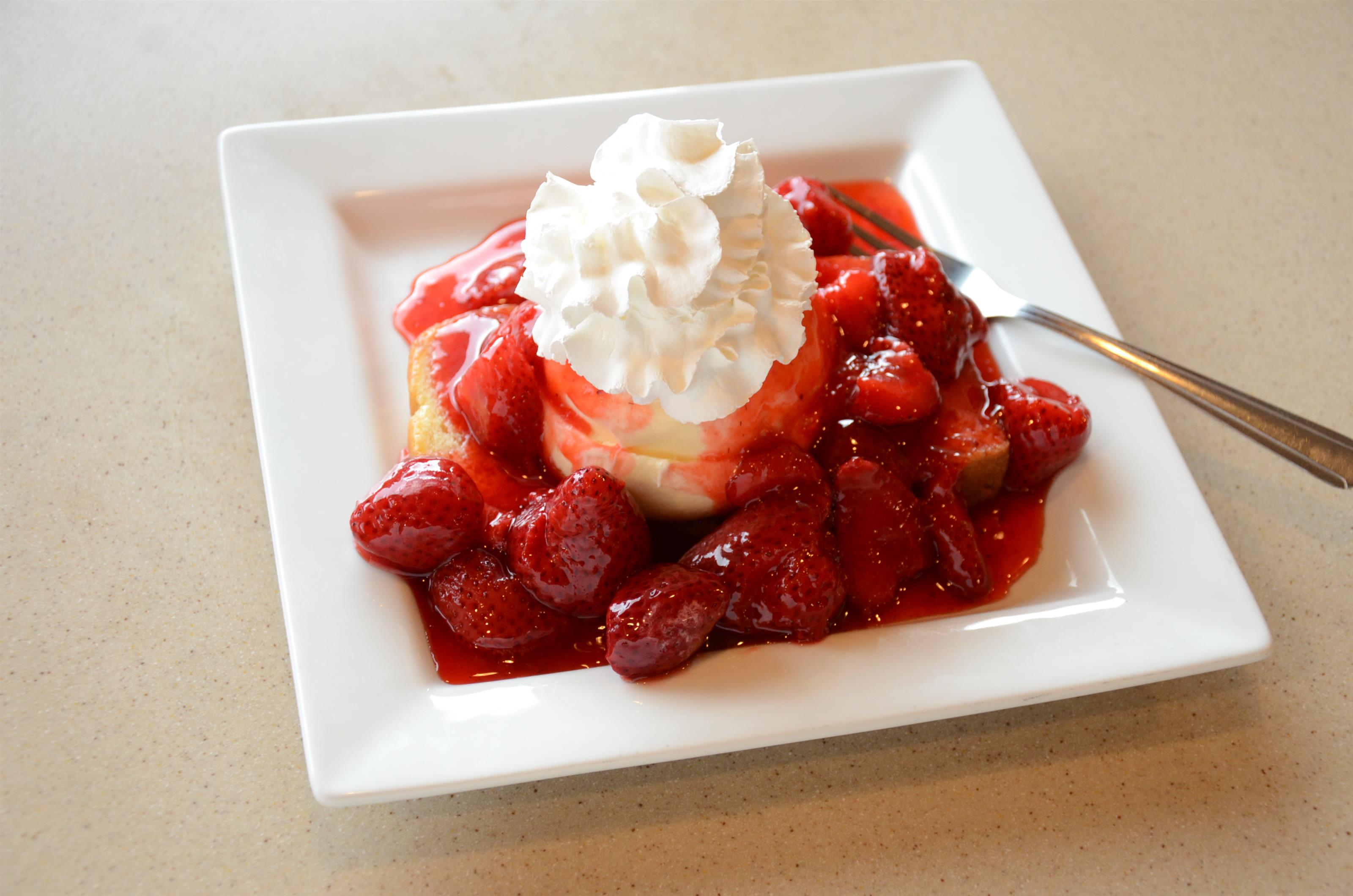 strawberry cheesecake with whole strawberries and whipped cream