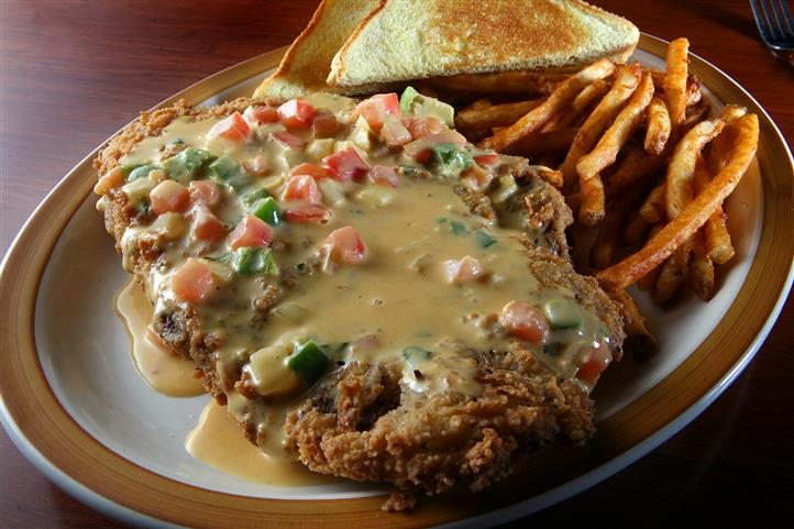Fried chicken topped with gravy with a side of toast and french fries