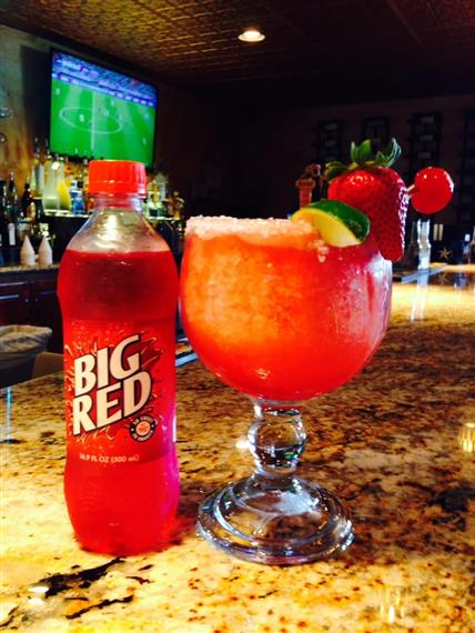 big red in a bottle next to an alcoholic beverage with lime, strawberry and cherry garnish on the bartop