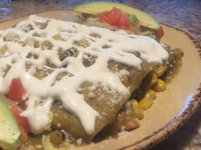 enchiladas covered in white sauce on a bed of corn